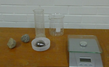 2 Rocks of similar size, a metal ball, graduated cylinder, beaker, tray, and balance