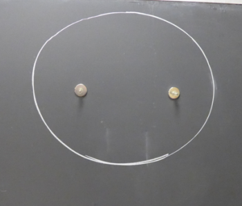 two magnets in a circle drawn on the chalkboard