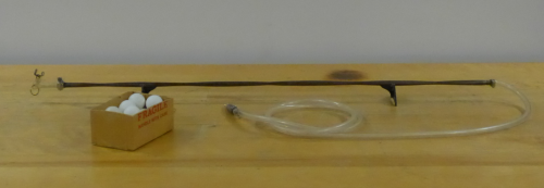 The tube of changing diameter rests next to a box of ping pong ballls