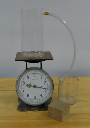 A large container rests on an antique scale.  A hose connected to the container drops into a second, smaller container