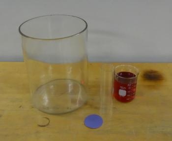 Large container, glass cylinder, plastic piece, beaker of colored water