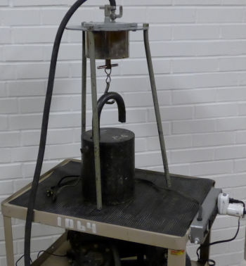 84-lb weight rests on a cart beneath a vacuum chamber apparatus.