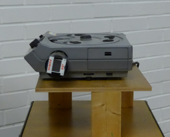 Slide projector with diffraction grating attached to lense