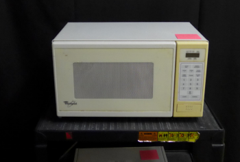 An old microwave on a cart