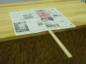 Newspaper covers half a piece of lath