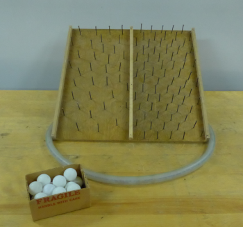 A board of nails, a hose, and a box of ping pong balls