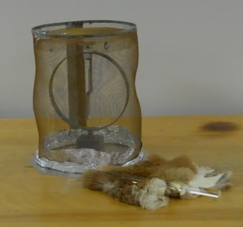 An electroscope is inside a Faraday cage.  Next to it, a piece of fur and rod are resting.
