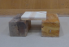 2 square boards are stacked and placed across a gap between 2 large wooden blocks