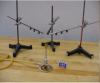 3 ring stands with rods of different metals.  The rods have balls attached by wax.  All three rods converge over a bunsen burner