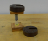 1-kg mass atop a piston made from a syringe and wood blocks; an extra weight rests nearby