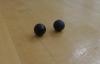 2 black balls rest on a table