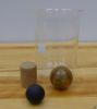2000-mL beaker, black rubber ball, colored bouncy ball, wooden cylinder.