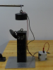 A small electromagnet is suspended above a plate attached to a 25-lb weight.