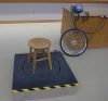 A stool rests on a rotating platform.  Nearby, a bicycle wheel rests near a foot pedal-driven motor.