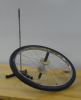 A bicycle wheel rests on a bench next to a ring stand with a pointed tip