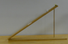 A wooden board connected with a hinge to another board is propped at a 70 degree angle with a ball on the outer edge.