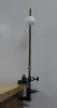 A rod with a spring is clamped to a bench; a whiffle ball rests on top of the spring