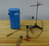 A dewar of liquid nitrogen, a metal ball suspended from a stand rod, a meeker burner, and 2 metal rings rest on a bench